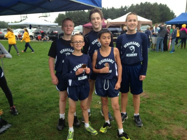 Five cross-country athletes taking a photo at a cross-country meet.